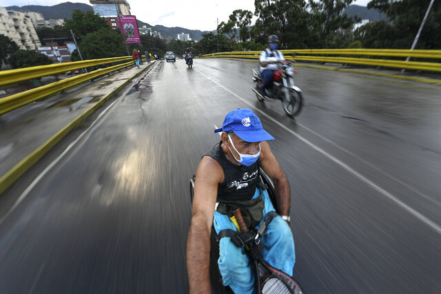 Manuel Mendoza hitches a ride in his wheelchair by grabbing on to the back of a motorcycle in the La Paz neighborhood of Caracas, Venezuela, Monday, Nov. 9, 2020. Moving from one point to another usually takes hours due to the lack of public transportation available for our condition. The Caracas subway is not an option.