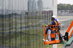 In this Nov. 7, 2019 photo, technicians prepare for the 2019 Brazilian Grand Prix at Interlagos racetrack in Sao Paulo, Brazil. Interlagos can host 60,000 fans per day. (AP Photo/Nelson Antoine)