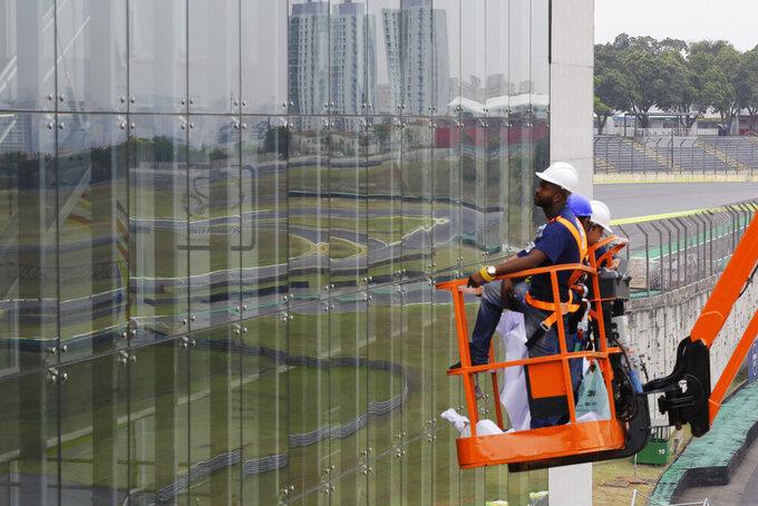 In this Nov. 7, 2019 photo, technicians prepare for the 2019 Brazilian Grand Prix at Interlagos racetrack in Sao Paulo, Brazil. Interlagos can host 60,000 fans per day. (AP Photo/Nelson Antoine)