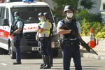 Police officers stand guard before a prison van carrying Hong Kong pro-democracy activist Andy Li leaves a court in Hong Kong, Wednesday, April 7, 2021. Li is one of the 12 young pro-democracy activists captured at sea last year by mainland Chinese authorities and returned to Hong Kong in March, as Li is charged with an offense under the newly-invented National Security Law. (AP Photo/Kin Cheung)