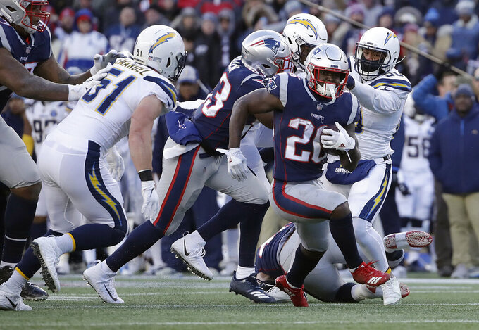 New England Patriots running back Sony Michel (26) runs from Los Angeles Chargers outside linebacker Kyle Emanuel (51) during the second half of an NFL divisional playoff football game, Sunday, Jan. 13, 2019, in Foxborough, Mass. (AP Photo/Elise Amendola)