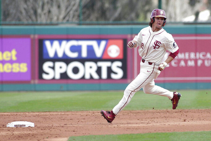 Florida State NCAA college baseball player Elijah Cabell runs to third during a game against the Univ. of Maine, Feb. 16, 2019, in Tallahassee, Fla. If all had gone as he hoped, Elijah Cabell and his Florida State teammates would be playing for the College World Series championship this week. Instead, Cabell treks to a ball field in his neighborhood in Winter Park, Florida, most days to work on his game in solitude. (Alicia Devine/Tallahassee Democrat via AP)