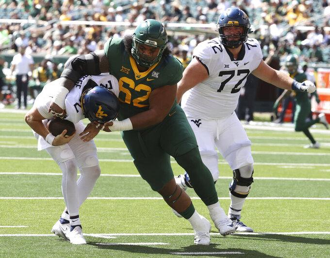 Baylor defensive tackle Siaki Ika sacks West Virginia quarterback Jarret Doege in the first half of an NCAA college football game, Saturday, Oct. 9, 2021, in Waco, Texas. (Rod Aydelotte/Waco Tribune-Herald via AP)