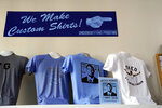 """Tee-shirts showing a likeness of former North Carolina basketball players Theo Pinson and Jackie Manuel are seen for sale at Underground Printing in Chapel Hill, N.C., Thursday, July 15, 2021. The Ann Arbor-based company Underground Printing is positioned to help athletes and its business make money with merchandise it can sell online. """"It's the same service that students and groups and departments use anyway so this is just an avenue for athletes to do the same thing,"""" said owner Rishi Narayan, whose company has 25 stores from Chapel Hill to Norman, Oklahoma. (AP Photo/Gerry Broome)"""