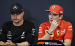 Ferrari driver Charles Leclerc of Monaco, right, is flanked by Mercedes driver Valtteri Bottas of Finland as they attend a news conference at the Monaco racetrack, in Monaco, Wednesday, May 22, 2019. The Formula one race will be held on Sunday. (AP Photo/Luca Bruno)