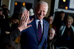 FILE - In this Jan. 5, 2020, file photo Democratic presidential candidate, former Vice President Joe Biden high-fives a member of the audience during a campaign rally at Modern Woodmen Park in Davenport, Iowa Biden has won the last few delegates he needed to clinch the Democratic nomination for president. (AP Photo/Andrew Harnik, File)