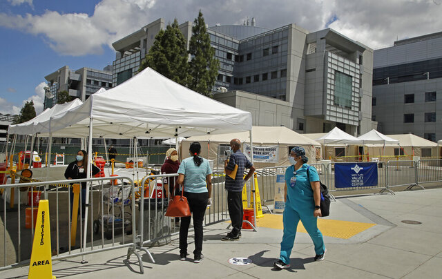 A healthcare worker walks past people waiting to be tested for COVID-19 on Tuesday, May 19, 2020, at Santa Clara Valley Medical Center in San Jose, Calif. Confirmed COVID-19 patients in Bay Area hospitals has dropped by more than half since the peak of 471 reported on April 7. (AP Photo/Ben Margot)