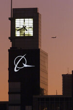 FILE - This Dec. 20, 2001 file photo shows an airplane flying past the Boeing logo on the company's headquarters in Chicago. The FAA's oversight duties are coming under greater scrutiny after deadly crashes involving Boeing 737 Max jets owned by airlines in Ethiopia and Indonesia, killing a total of 346 people. The U.S. was nearly alone in allowing the planes to keep flying until it relented on Wednesday, March 13, 2019, after getting satellite evidence showing the crashes may be linked. (AP Photo/Ted S. Warren, File)