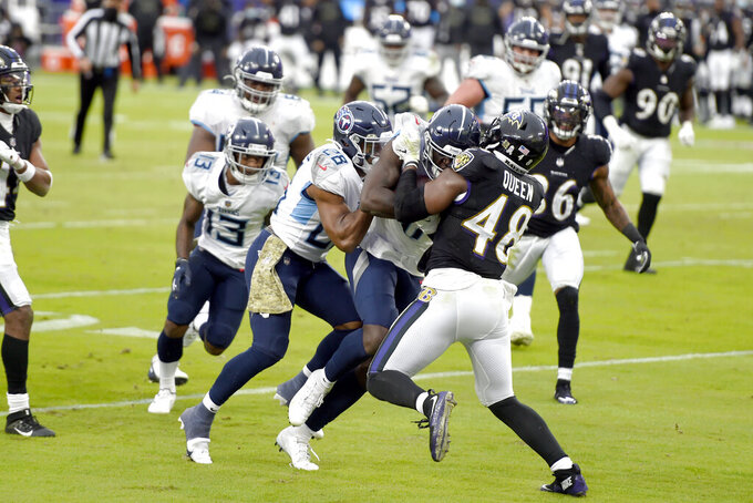 Tennessee Titans wide receiver A.J. Brown, center, is pushed by teammate Jeremy McNichols, left, while Baltimore Ravens inside linebacker Patrick Queen (48) tries to stop them on a touchdown catch and run during the second half of an NFL football game, Sunday, Nov. 22, 2020, in Baltimore. (AP Photo/Gail Burton)