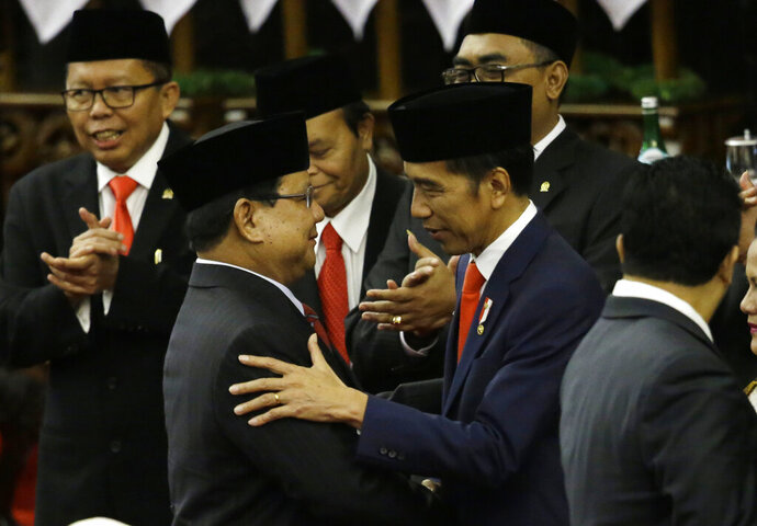 Indonesian President Joko Widodo, right, is congratulated by the Chairman of Gerindra Party who is also his former rival in April's election Prabowo Subianto during his swearing-in ceremony at the parliament building in Jakarta, Indonesia, Sunday, Oct. 20, 2019. Indonesian President Joko Widodo, who rose from poverty and pledged to champion democracy, fight entrenched corruption and modernise the world's most populous Muslim-majority nation, was sworn in Sunday for his second and final five-year term with a pledge to take bolder actions. (AP Photo/Achmad Ibrahim, Pool)
