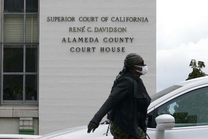 FILE - In this March 9, 2021, file photo, a pedestrian wears a face mask while walking across the street from the Alameda County Court House during the coronavirus outbreak in Oakland, Calif. The official COVID-19 death count in Alameda County, in the San Francisco Bay Area, fell from 1,634 to 1,223 after officials changed the criteria for fatalities to match state and national definitions, the county's public health department said in a news release. The county will now only report deaths as coronavirus-related fatalities when people died as a direct result of COVID-19, or had the virus as a contributing cause of death as well as people for whom COVID-19 could not be ruled out as a cause of death. (AP Photo/Jeff Chiu, File)