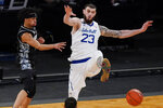 Georgetown's Dante Harris, left, passes the ball away from Seton Hall's Sandro Mamukelashvili (23) during the second half of an NCAA college basketball game in the semifinals in the Big East men's tournament Friday, March 12, 2021, in New York. (AP Photo/Frank Franklin II)