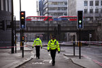 Police officers patrol the scene of the deadly stabbings at London Bridge, in London, Saturday, Nov. 30, 2019. UK counterterrorism police on Saturday searched for clues into how a man imprisoned for terrorism offenses before his release last year managed to stab several people before being tackled by bystanders and shot dead by officers on London Bridge. (AP Photo/Alberto Pezzali)