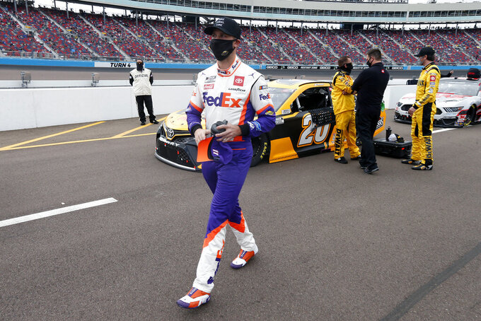 Denny Hamlin walks down pit road prior to the NASCAR Cup Series auto race at Phoenix Raceway, Sunday, Nov. 8, 2020, in Avondale, Ariz. (AP Photo/Ralph Freso)