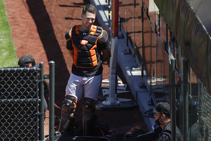 San Francisco Giants catcher Buster Posey, top, talks with manager Gabe Kapler, bottom right, during a baseball practice in San Francisco, Sunday, July 5, 2020. (AP Photo/Jeff Chiu)