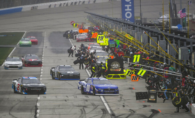 Tyler Reddick (20), Jeffrey Earnhardt (18), and Cole Cluster (00) pull to the front while making a pit stop with other drivers during a NASCAR Xfinity auto race at Atlanta Motor Speedway, Saturday, Feb. 23, 2019, in Hampton, Ga. (AP Photo/John Amis)