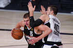 Denver Nuggets' Nikola Jokic (15) tries to get past Los Angeles Clippers' Ivica Zubac (40) during the second half of an NBA conference semifinal playoff basketball game Monday, Sept. 7, 2020, in Lake Buena Vista, Fla. (AP Photo/Mark J. Terrill)