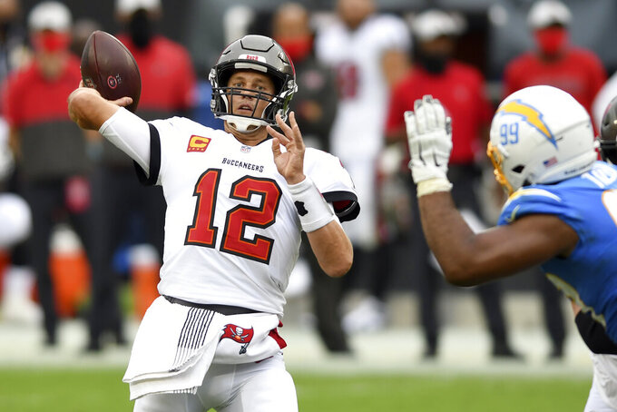 Tampa Bay Buccaneers quarterback Tom Brady (12) throws a pass as he is pressured by Los Angeles Chargers defensive tackle Jerry Tillery (99) during the first half of an NFL football game Sunday, Oct. 4, 2020, in Tampa, Fla. (AP Photo/Jason Behnken)