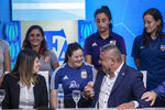Claudio Tapia, president of Argentina's Soccer Federation, greets a soccer player during a press conference to announce the early implementation of a plan to professionalize women's soccer in Buenos Aires, Argentina, Saturday, March 16, 2019. Almost 90 years after men's soccer turned professional in Argentina, the women's game is still being played by amateur athletes who get little to no money for their work on the field. (AP Photo/Daniel Jayo)