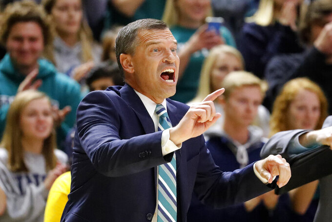 UNC Wilmington head coach C. B. McGrath coaches from the sideline during the first half of an NCAA college basketball game  against North Carolina in Wilmington, N.C., Friday, Nov. 8, 2019. (AP Photo/Karl B DeBlaker)