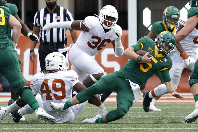 Baylor's Charlie Brewer (5) is sacked by Texas' Ta'Quon Graham (49) during the second half of an NCAA college football game in Austin, Texas, Saturday, Oct. 24, 2020. (AP Photo/Chuck Burton)