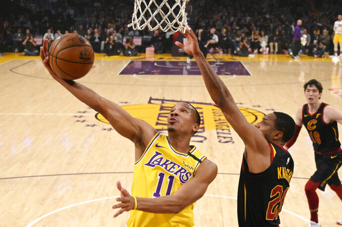 FILE - In this Jan. 13, 2020, file photo, Los Angeles Lakers guard Avery Bradley, left, shoots as Cleveland Cavaliers guard Brandon Knight defends during the first half of an NBA basketball game in Los Angeles. Bradley still has serious concerns about the coronavirus, particularly because one of his children has struggled with respiratory illnesses. Those concerns kept him from the NBA's restart bubble. They won't keep him from this season. Bradley has finalized his new contract with the Miami Heat and says he will be ready to go when camp starts next week. (AP Photo/Mark J. Terrill, File)