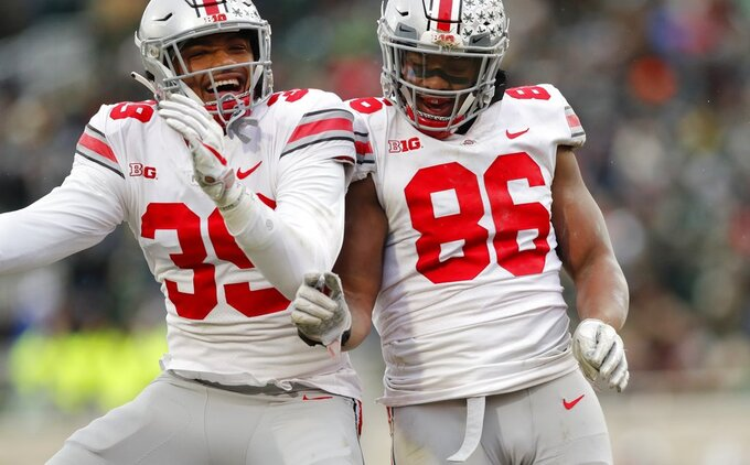 Ohio State linebacker Malik Harrison (39) and defensive tackle Dre'Mont Jones (86) celebrate after Jones' fumble recovery at the 2-yard line during the second half of an NCAA college football game against the Michigan State, Saturday, Nov. 10, 2018, in East Lansing, Mich. (AP Photo/Carlos Osorio)