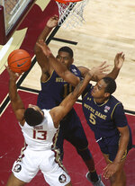 Florida State guard Anthony Polite (13) has his layup blocked by Notre Dame guard D.J. Harvey (5) as forward Juwan Durham (11) also defends in the first half of an NCAA college basketball game in Tallahassee, Fla., Monday, Feb. 25, 2019. (AP Photo/Phil Sears)