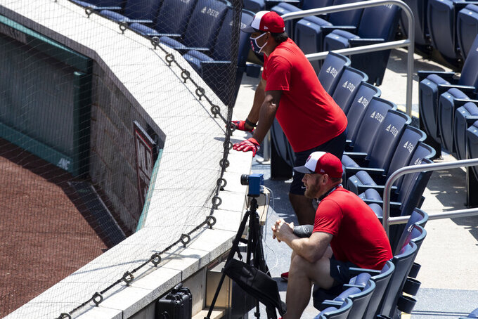 Washington Nationals manager Dave Martinez, rear, wears a mask as he watches from the stands with starting pitcher Stephen Strasburg during a baseball training camp workout at Nationals Park, Wednesday, July 8, 2020, in Washington. (AP Photo/Alex Brandon)