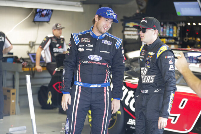NASCAR Xfinity Series drivers Chase Briscoe and Noah Gragson talk in the garage area before the start of NASCAR Xfinity auto racing practice at Indianapolis Motor Speedway, Friday, Sept. 6, 2019 in Indianapolis. (AP Photo/Michael Conroy)