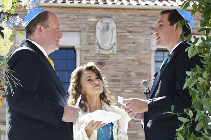 In this photo provided by Jocelyn Augustino, Rabbi Tirzah Firestone, center, officiates a traditional Jewish wedding ceremony attended by family and friends for Colorado Gov. Jared Polis, left, and his partner, Marlon Reis, in Boulder, Colo. on Wednesday Sept. 15, 2021. Polis, who became the first openly gay man in the United States to be elected governor in 2018, married his longtime partner and first gentleman Reis, a writer and animal welfare advocate. (Jocelyn Augustino via AP)