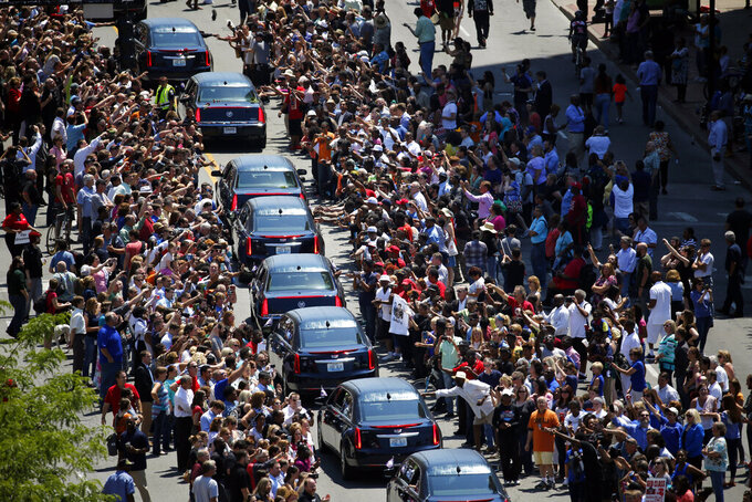 FILE - Muhammad Ali's funeral procession passes as onlookers line the street in Louisville, Ky., in this Friday, June 10, 2016, file photo. Five years after his death, residents, as well as Ali's daughter, Rasheda Ali, look back at the legacy of the boxer and the ways the people of Louisville have come together since his passing.  (AP Photo/Jeff Roberson, File)