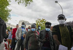 People lining up to be vaccinated at a tent site set up by Doctors Without Borders to vaccinate migrants, the homeless and other marginalized populations in Paris, Thursday, July 29, 2021. Vaccination rates are picking up again in France as the government requires a virus pass for more and more activities, but social workers worry that the measure will further marginalize migrants and other poor populations. (AP Photo/Michel Euler)