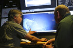 In this Wednesday, Oct. 16, 2019 photo, Vulcan Inc. director of undersea operations for the Petrel, Rob Kraft, left, and the Naval History and Heritage Command's Frank Thompson, left, look at footage of the Japanese aircraft carrier Kaga, off Midway Atoll in the Northwestern Hawaiian Islands. Deep-sea explorers scouring the world's oceans for sunken World War II ships are honing in on a debris field deep in the Pacific. The research vessel called the Petrel is launching underwater robots about halfway between the U.S. and Japan in search of warships from the Battle of Midway.  (AP Photo/Caleb Jones)