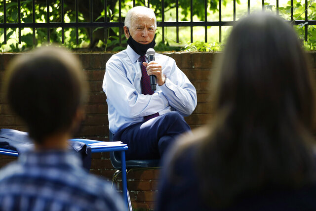 FILE - In this June 25, 2020, file photo, Democratic presidential candidate former Vice President Joe Biden, center, speaks to Stacie Ritter, right, and her son, Jan, during a meeting with families who have benefited from the Affordable Care Act in Lancaster, Pa.(AP Photo/Matt Slocum, File)