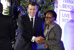 France's President Emmanuel Macron, center, shakes hands with Joyce Msuya, Deputy Executive Director of the United Nations Environment Programme, center-right, at the United Nations Environment Assembly in Nairobi, Kenya Thursday, March 14, 2019. Macron said at the conference Thursday that energy resources like coal that fueled industrialization in the developed world are no longer viable because they create pollution. (AP Photo/Khalil Senosi)