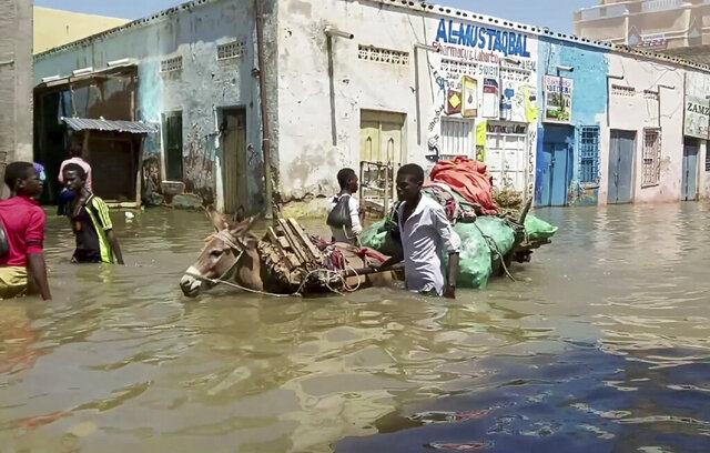 In this image made from video taken Sunday, May 17, 2020, people wade through a flooded street in Beledweyne, central Somalia. Flooding in central Somalia has affected nearly 1 million people, displacing about 400,000, the United Nations said Monday, May 18, 2020 warning of possible disease outbreaks because of crowding where the displaced are seeking temporary shelter. (AP Photo)