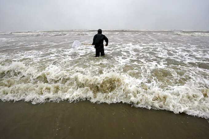 Daniel fishes in the Gulf of Mexico as winds from what was Hurricane Nicholas continue to push waves closer to shore Tuesday, Sept. 14, 2021, in Galveston, Texas. (AP Photo/David J. Phillip)