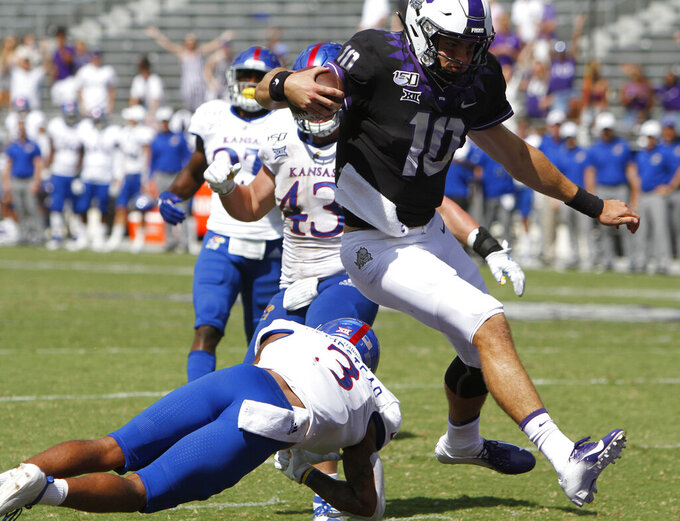 TCU Horned Frogs quarterback Mike Collins (10) leaps past Kansas Jayhawks cornerback Elmore Hempstead Jr. (3) to score on the last play of the game as the Kansas Jayhawks played the TCU Horned Frogs at Amon Carter Stadium in Fort Worth, Texas Saturday, Sept. 28, 2019.  (David Kent/Star-Telegram via AP)