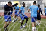 In this Saturday, May 4, 2019, Francis Kalombo from Congo, center, practices with his teammates of Aiolikos during a training session at the Municipality stadium of Mytilene, on the northeastern Aegean island of Lesbos, Greece. Kalombo became the first refugee to sign for a professional Greek soccer club. A 10-minute walk from Europe's largest refugee camp sits a nondescript yet remarkable soccer field. It's a place where residents of the Moria camp on the Greek island of Lesbos can briefly forget about their tiny container-homes and crowded tents and instead worry about corner kicks and throw-ins. And it's the place where 15-year-old Francis Kalombo became the first refugee to sign for a professional Greek soccer club. (AP Photo/Thanassis Stavrakis)