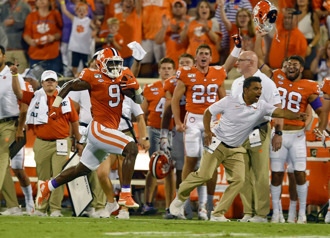 FILE - In this Aug. 29, 2019, file photo, Clemson's Travis Etienne runs down the sideline for a 90-yard touchdown during the first half of an NCAA college football game against Georgia Tech, in Clemson, S.C. Clemson is preseason No. 1 in The Associated Press Top 25, Monday, Aug. 24, 2020, a poll featuring nine Big Ten and Pac-12 teams that gives a glimpse at what's already been taken from an uncertain college football fall by the pandemic. (AP Photo/Richard Shiro, File)
