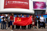 Visitors to the 21st China Beijing International High-tech Expo pose for photos with a Chinese flag in Beijing, China, Thursday, May 17, 2018. The Trump administration has threatened to impose tariffs on up to $150 billion in Chinese imports to punish Beijing over trade practices requiring American companies to hand over technology in exchange for access to the Chinese market. China has counterpunched by targeting $50 billion in U.S. products. (AP Photo/Ng Han Guan)