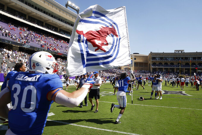 SMU wide receiver Rashee Rice (11), followed by linebacker Brian Holloway (30) runs the SMU flag to midfield after they defeated TCU a NCAA football game in Fort Worth, Texas, Saturday, Sept. 25, 2021. (AP Photo/Michael Ainsworth)