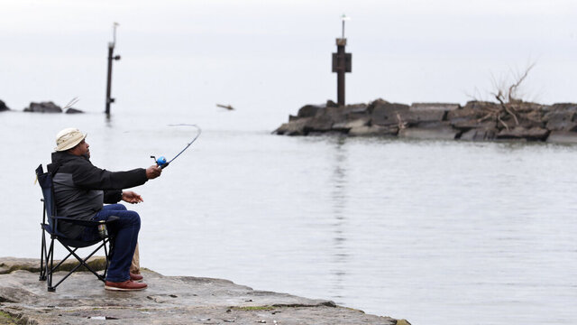 Corey Stacey casts his fishing line on the shores of Lake Erie at Wildwood Park, Tuesday, April 7, 2020, in Cleveland. (AP Photo/Tony Dejak)
