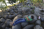 A man rests next the Suchiate River in Ciudad Hidalgo, on the Mexican border with Guatemala, Sunday, Jan. 19, 2020. Mexican authorities have closed a border entry point in southern Mexico after thousands of Central American migrants tried to push across a bridge between Mexico and Guatemala. (AP Photo / Marco Ugarte)
