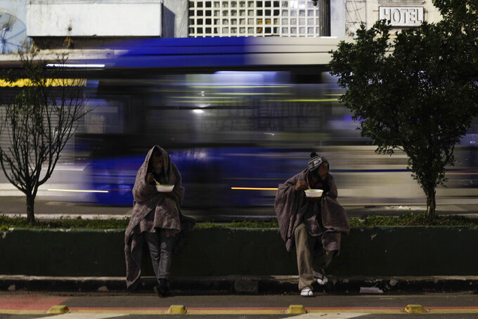 Homeless people sit outside amid historically cold weather as they eat a hot meal donated by a church in Sao Paulo, Brazil, early Friday, July 30, 2021. The Brazilian government's meteorological institute says low temperatures should endure until the start of August. (AP Photo/Marcelo Chello)
