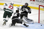 Los Angeles Kings goaltender Jonathan Quick, right, cannot stop a goal by Minnesota Wild defenseman Jonas Brodin (not shown) as center Nick Bjugstad, left and center Blake Lizotte, center, watch the puck during the first period of an NHL hockey game in Los Angeles, Thursday, Jan. 14, 2021. (AP Photo/Alex Gallardo)