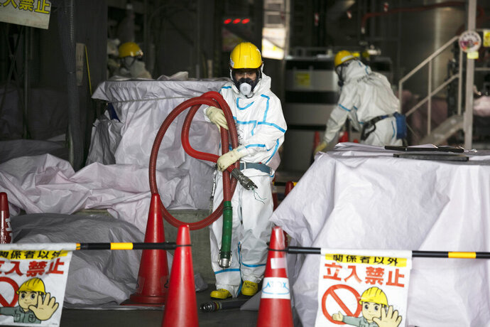FILE - In this Feb. 12, 2020, file photo, a worker in a hazmat suit carries a hose while working at a water treatment facility at the Fukushima Dai-ichi nuclear power plant in Okuma, Fukushima Prefecture, Japan. Japanese Prime Minister Yoshihide Suga said Wednesday, Oct. 28, that his government is carefully working on final details on a release of the massive amount of treated but still radioactive water from the wrecked Fukushima nuclear plant, after a speculated decision of a release to the sea by the end of October has triggered fierce protests from fishermen around the country. (AP Photo/Jae C. Hong, File)