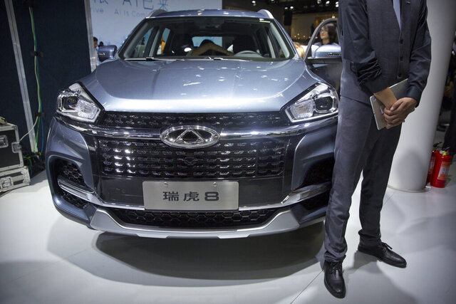 FILE - In this April 25, 2018, file photo a staff member stands next to a Tiggo 8 SUV by Chinese automaker Chery after a press conference at the China Auto Show in Beijing. A California company says it will build and sell Chinese-designed automobiles in the U.S. at the end of next year or early in 2022. HAAH Automotive Holdings says it has an agreement with large Chinese automaker Chery Automobile to provide the vehicles, which will be assembled in a U.S. factory. HAAH says the first vehicle sold will be a midsize SUV. (AP Photo/Mark Schiefelbein, File)