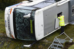 A police office looks into a school bus that has crashed in Berka Vor Dem Hainich, near Eisenach, Germany, Thursday, jan. 23, 2020. German media reported that two children died in a school bus crash in the central state of Thuringia early Thursday. Public broadcaster MDR reported that 20 children and the bus driver were injured in the crash in Berka, about 260 kilometers (160 miles) southwest of Berlin. (Swen Pfoertner/dpa via AP)